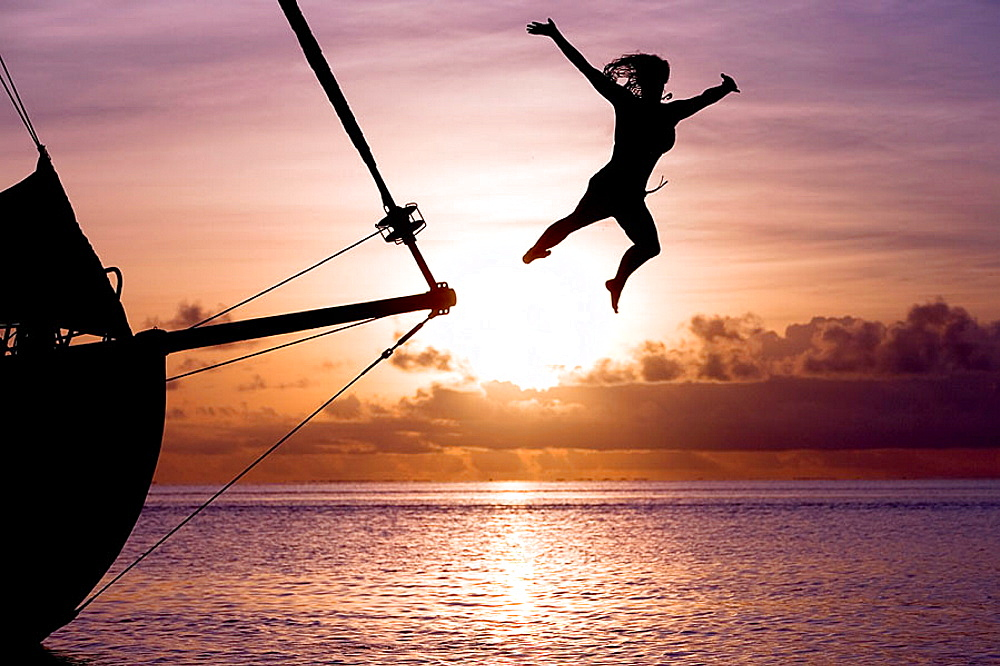 Girl jumping from yacht in sundown, Bora Bora, French Polynesia.