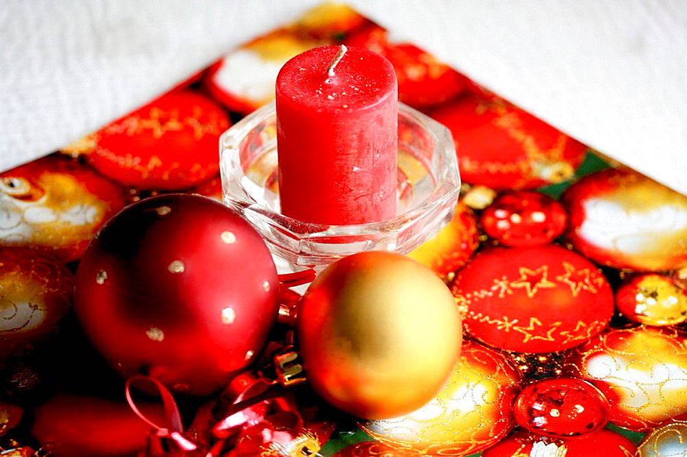 Red and gold Christmas ball with red candle on red and gold wrapping paper A red and a gold Christmas ball lie next to a red candle in a clear glss candle holder The wrapping paper has red and gold Christmas balls on it