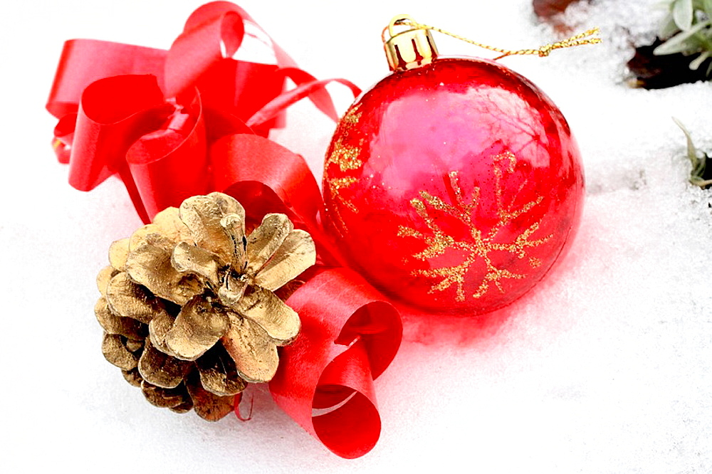Red Christmas ball with gilt pine cone and red ribbon in snow A red transparent ball with gold glitter snowflake on it lies in snow next to a gilt pine cone Red satin ribbon curls about them High color contrast of elements and textures