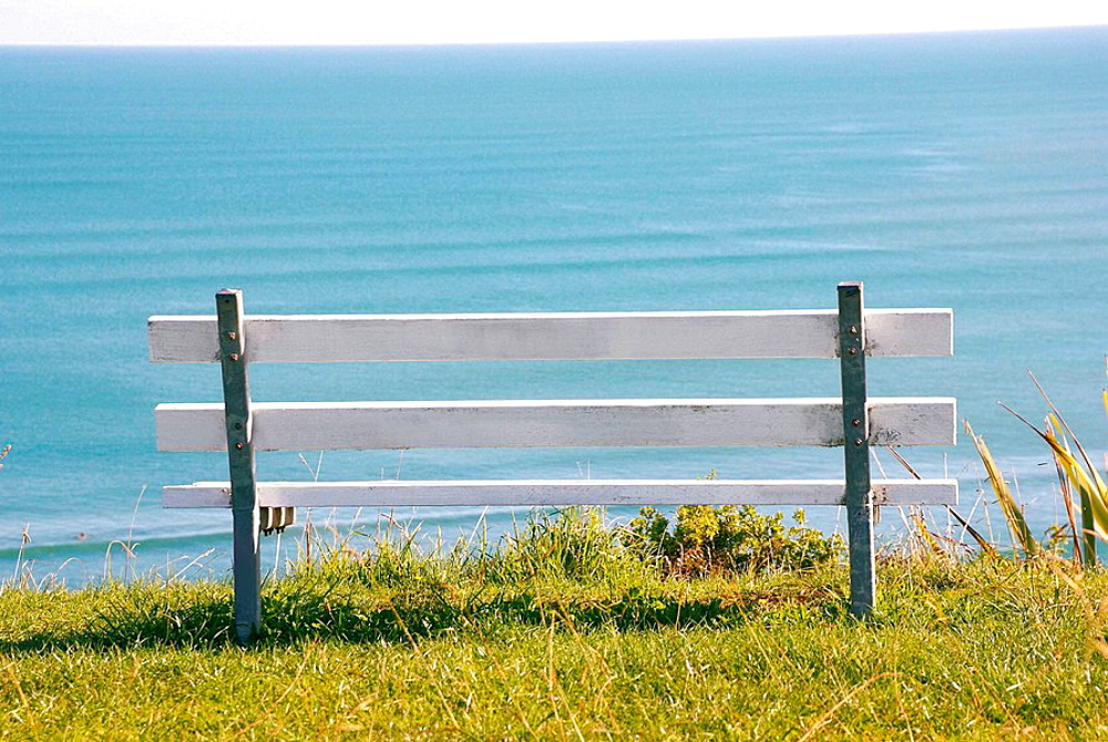 White wooden bench facing Wanuis beach landscape in Raglan, world famous surfing town in the Waikato region, New Zealand, North Island