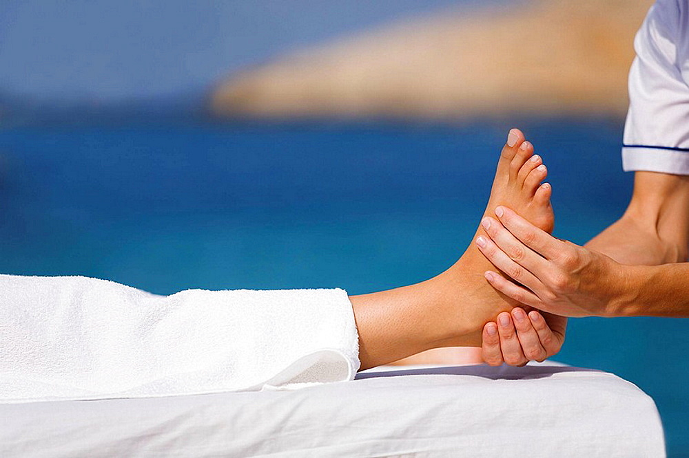 Woman having a feet massage by the sea