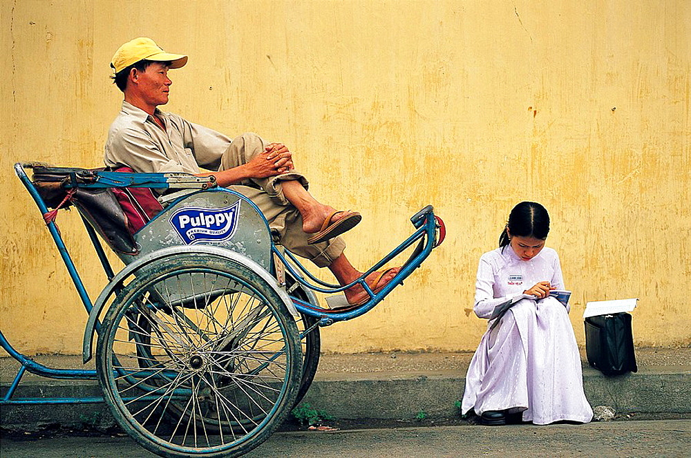 Cyclo driver and student waiting outside college albert sarrault, Saigon, Vietnam