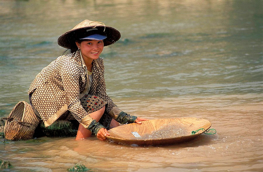 Young woman panning for gold at Mekong river, Laos