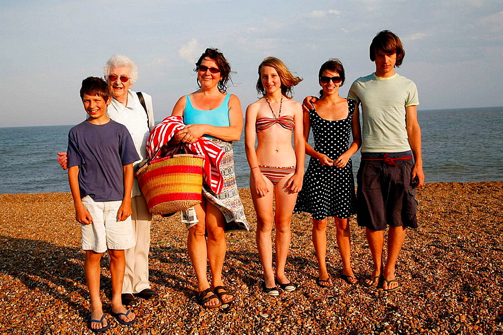 Women and children pose for family snap on a summer beach early evening light