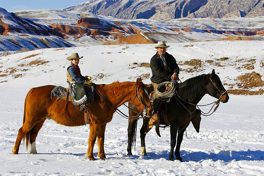 Father and son out for a winter ride, Shell, Wyoming, Usa