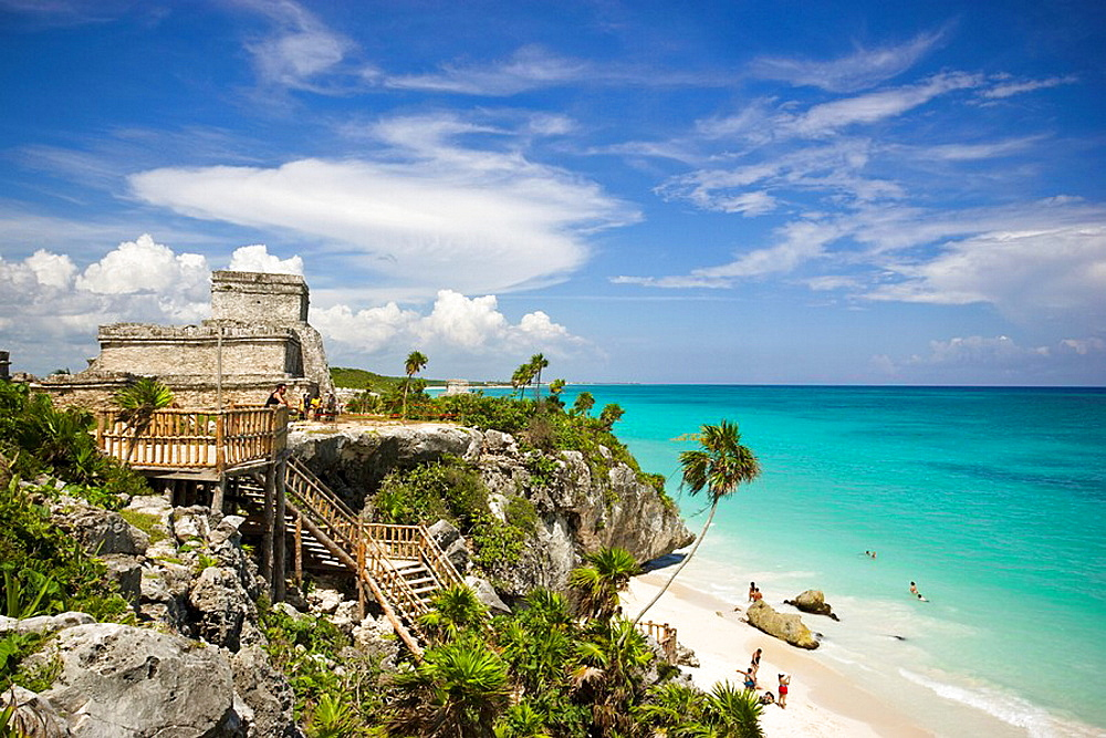 El Castillo The Castle and rocky beach with sunbathers at the Mayan ruins of Tulum in Quintana Roo, Mexico