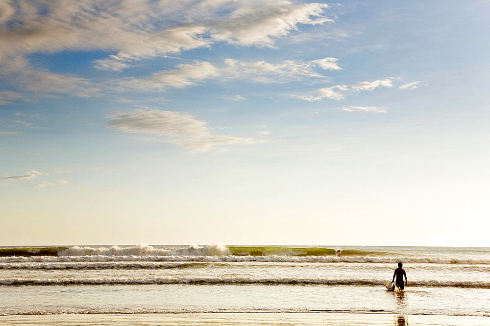 Surfer carrying his surfboard into the ocean in Dominical, Costa Rica