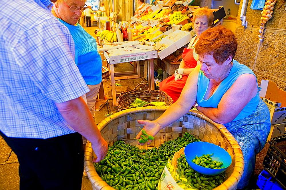 Saleswoman of `padronpeppers  In Abastos market  Santiago de Compostela  Coruna province Spain  Camino de Santiago