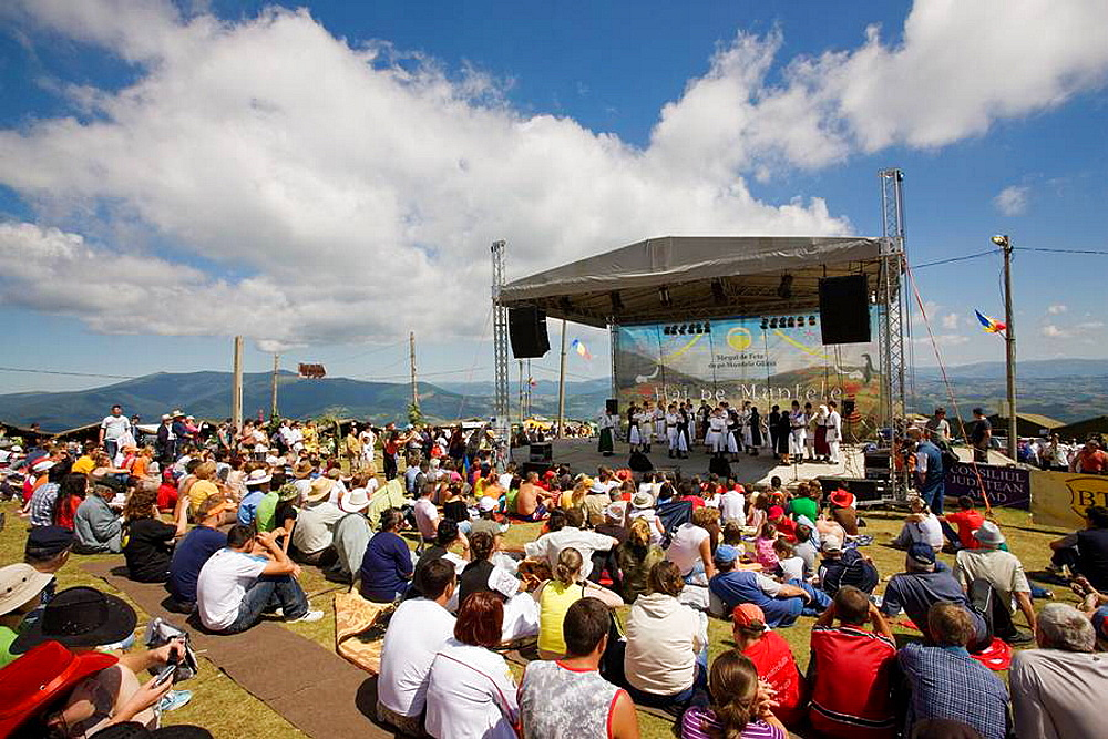 romanian folk music musician performing on folk music contest, visitors listening to performance  Targul de Fete de pe Muntele Gaina translated: Maidens Fair on the mountain Gaina is a traditional transsylvanian festival, where young people met, to f