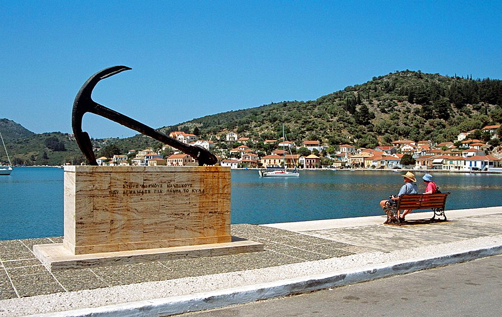 Anchor, tribute to those who have died at sea, and harbour, people on seat, Vathi, Ithaca, Greece
