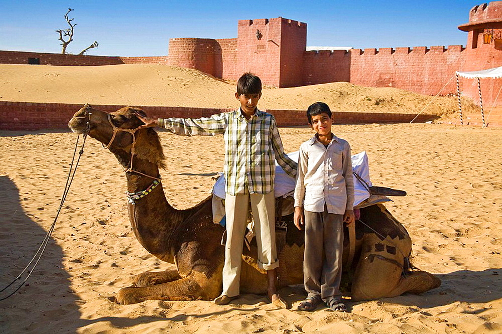 Camel and two young boys at Osian Camel Camp, Osian, Rajasthan, India
