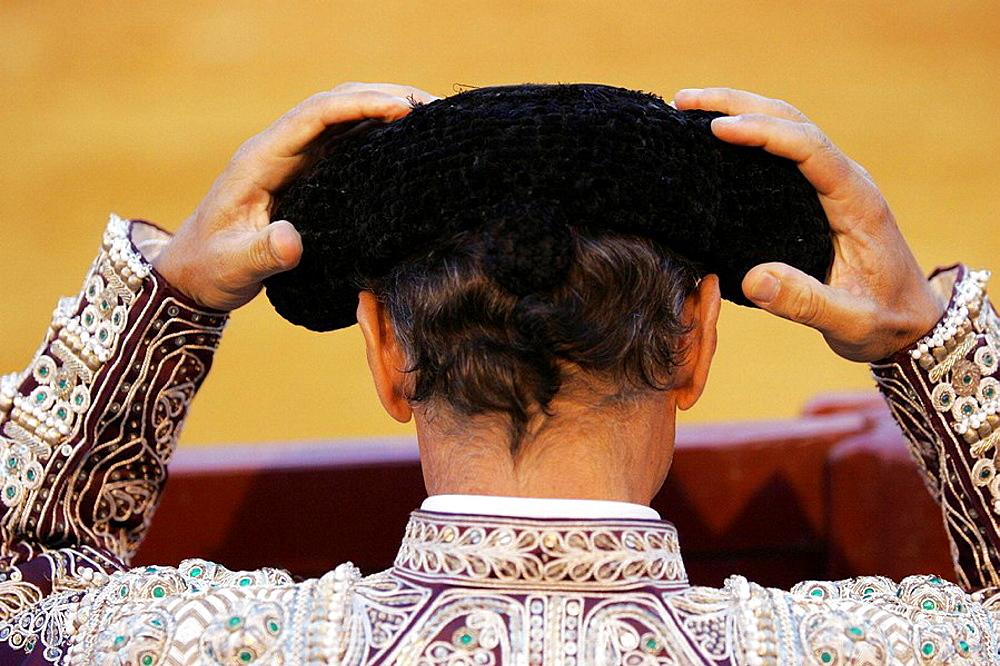 Bullfighter adjusting his montera (hat) before bullfighting in the Real Maestranza bullring, Seville, Spain