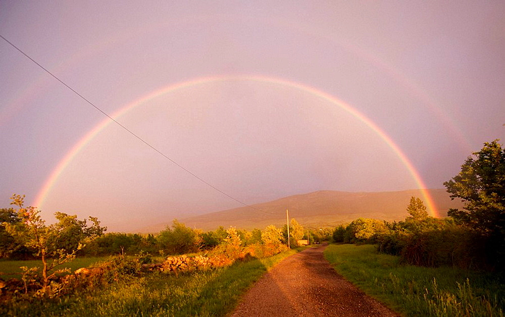 Double rainbow above road
