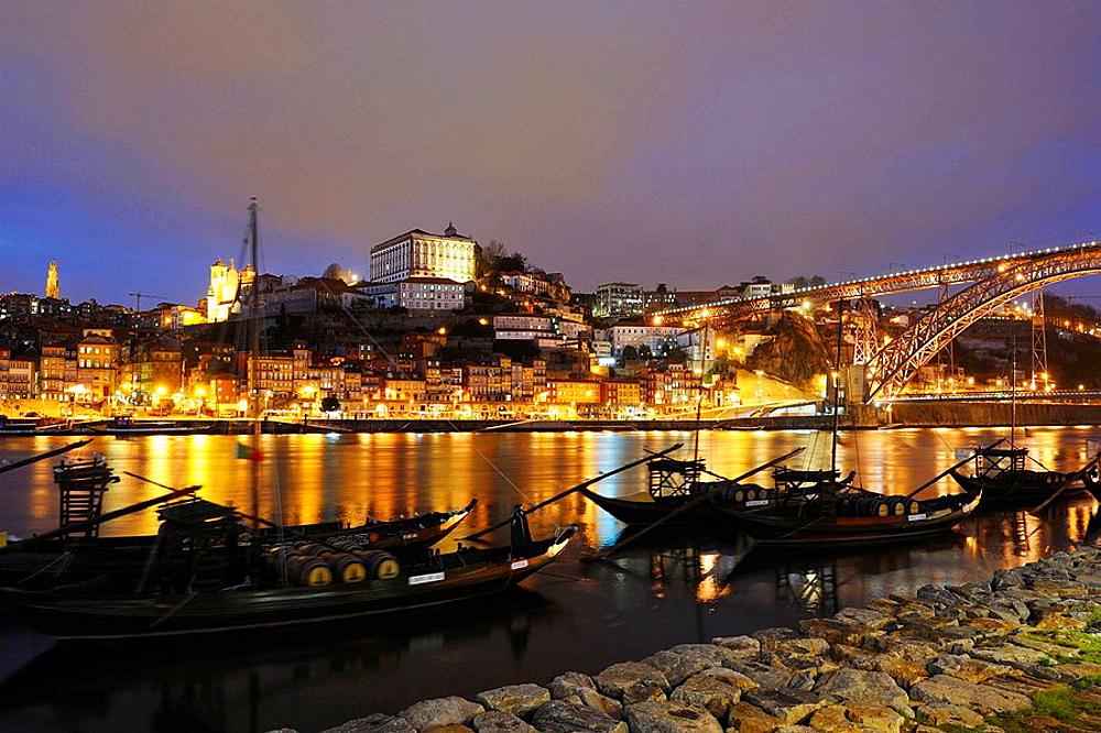 Rabelos' ancient boats for porto wine transport in front of cellars at Vila Nova De Gaia along Douro River near Dom Luiz I Bridge, Porto, Portugal