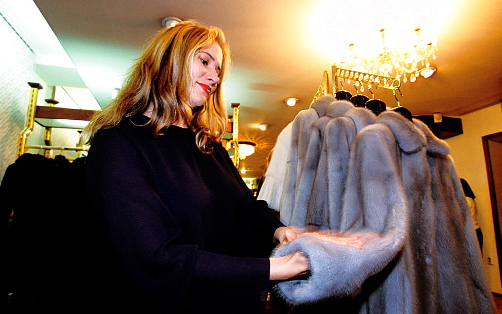 Wealthy woman choosing a fur at Helena's shop, St, Petersburg, Russia