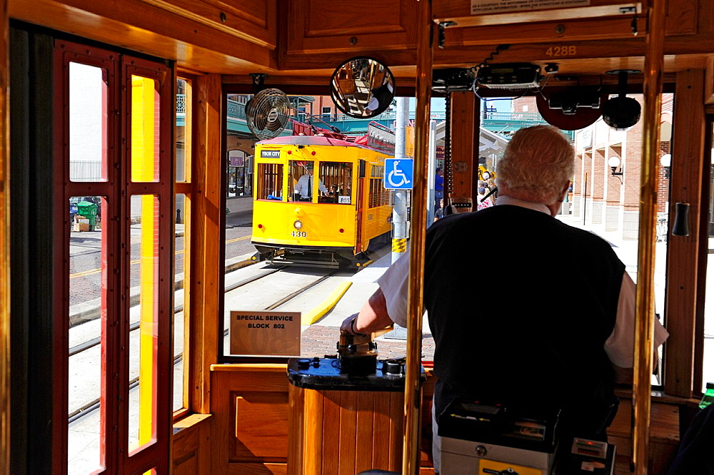 Conductor runs yellow historic trolley on track in Ybor City Tampa Florida