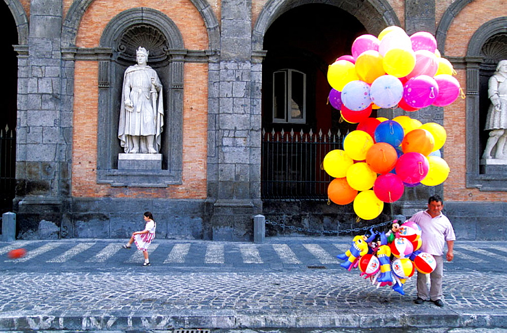 Girl playing football and balloons seller in front of Royal Palace, Naples, Italy
