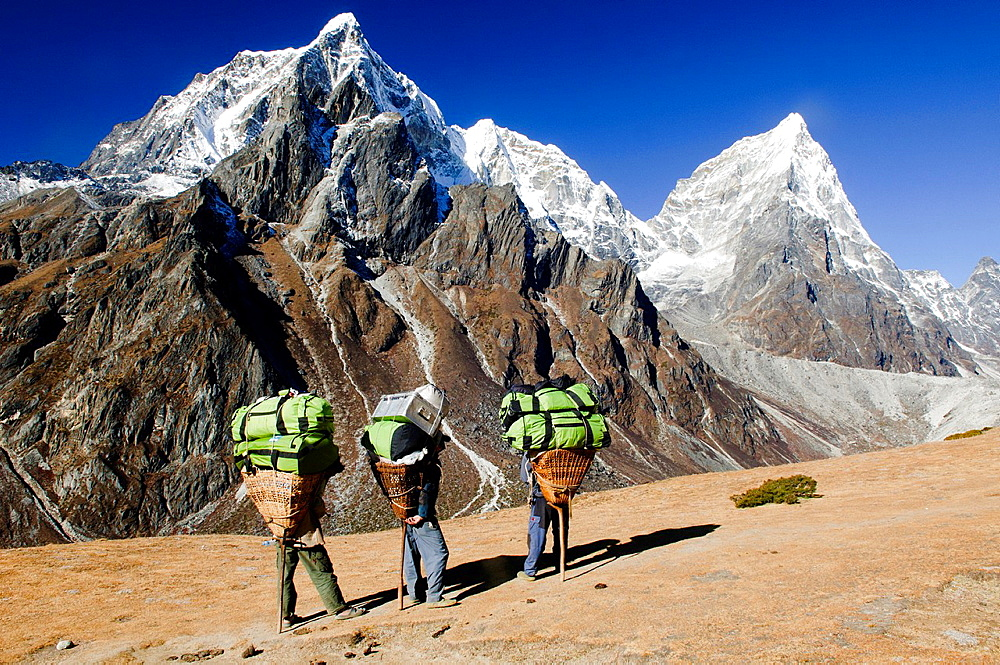 porters resting under Cholatse Peak in the Everest Region of Nepal