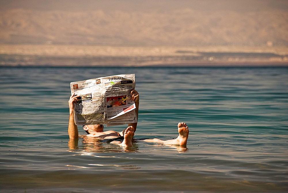 Man reading a newspaper while floating on the Dead sea, Jordan, Asia