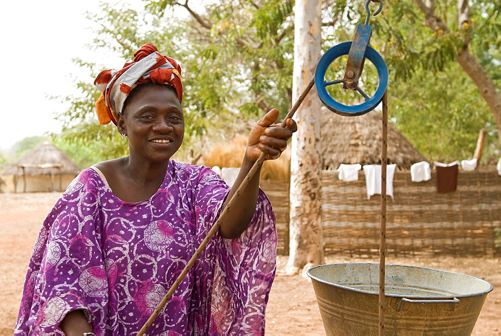 African Bassari women with headscarf hauling water from a well, Salemata village, Bassari country, Senegal, Africa