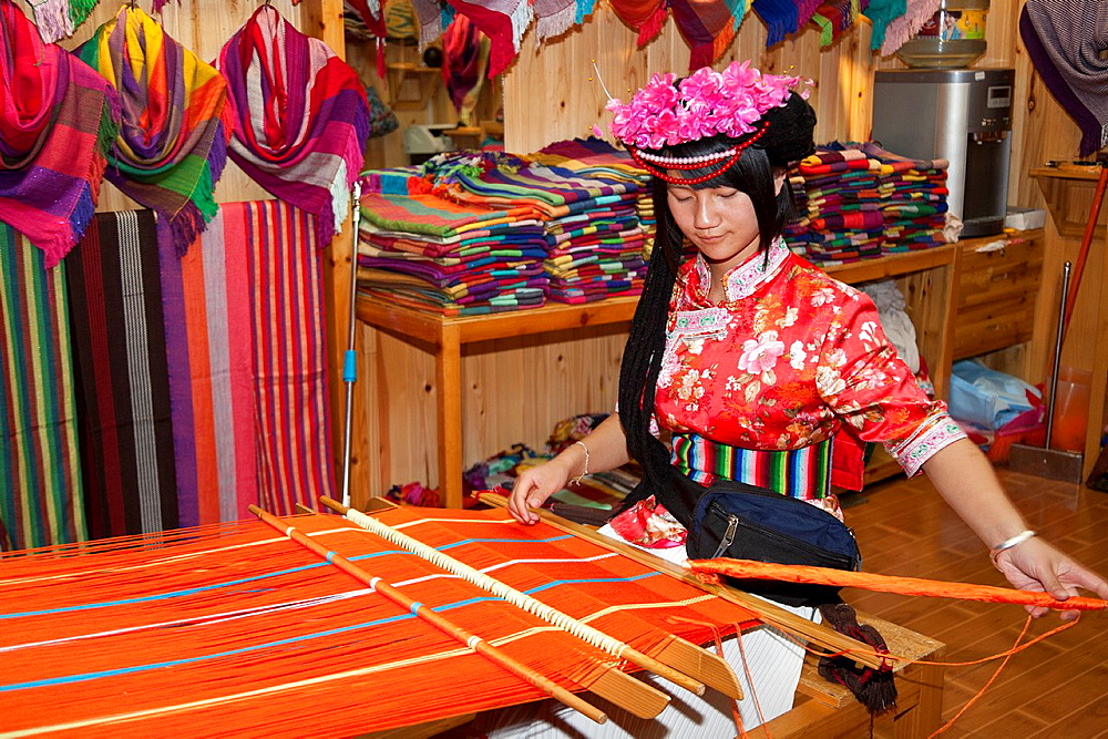 Mosuo woman weaving colourful clothing in her shop, Lijiang, Yunnan Province, China