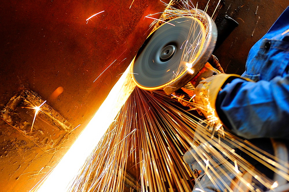 Close-up of heavy industry worker with grinding machine throwing a splash of sparks - 817-263149