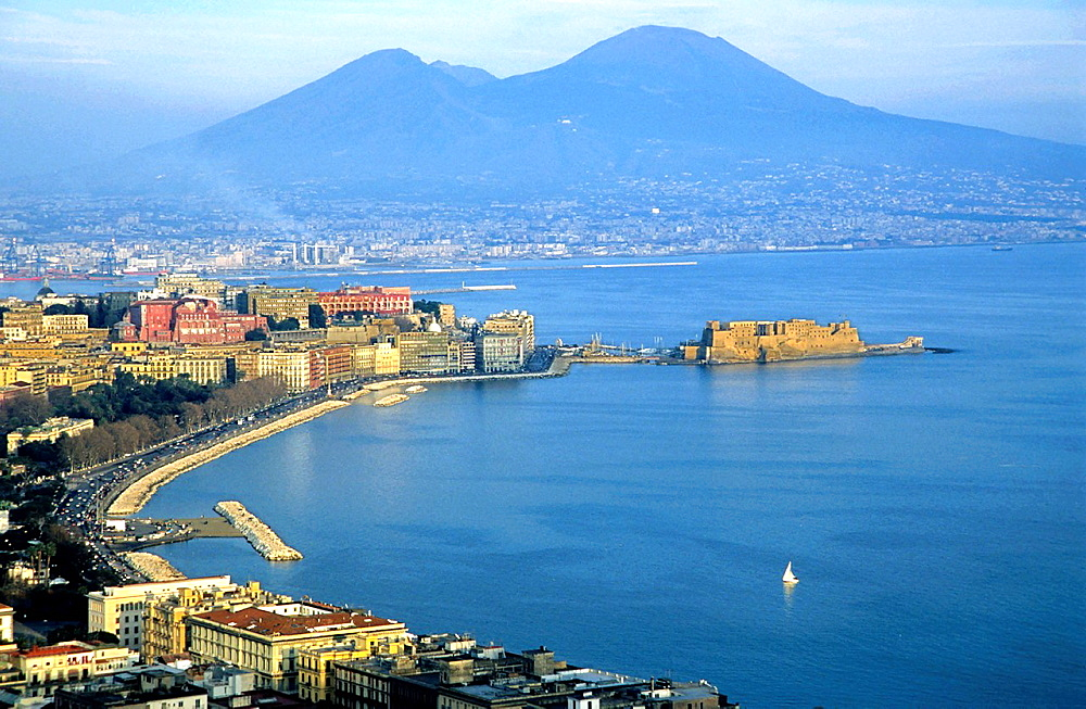 View across the Bay of Naples showing the Aragonese Castle on the peninsula of Ischia with the townscape and Mount Vesuvius in the background, Naples, Italy
