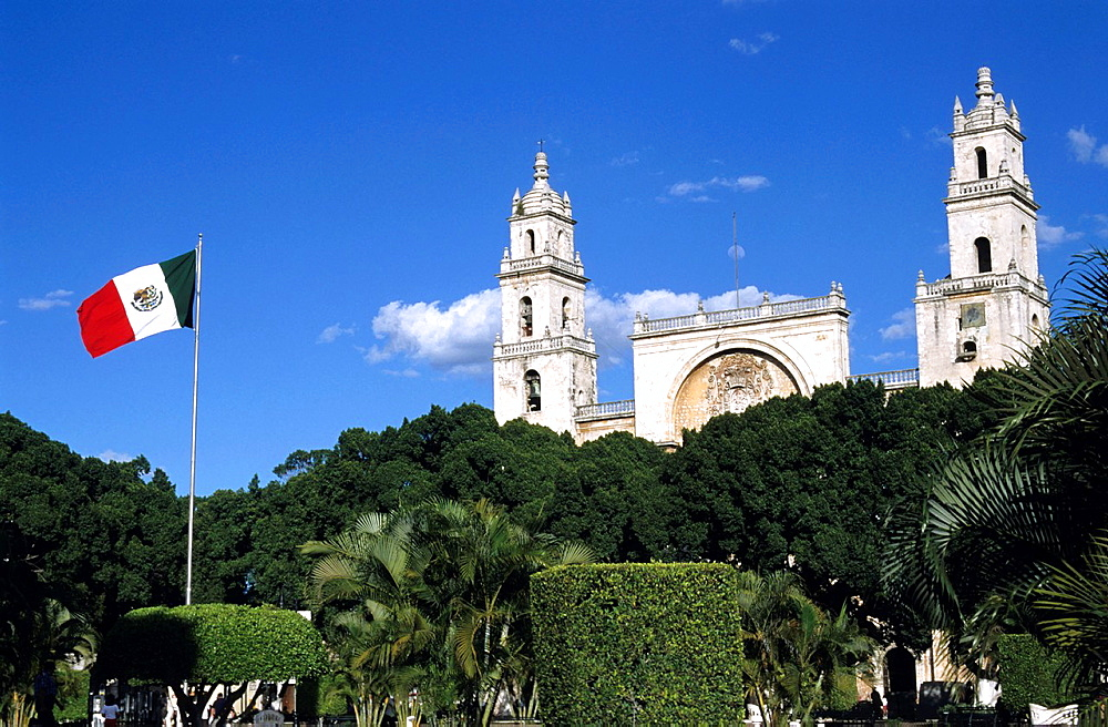 Mexican flag flying in formal garden of the city square with the cathedral facade in the background, Merida, Yucatan, Mexico