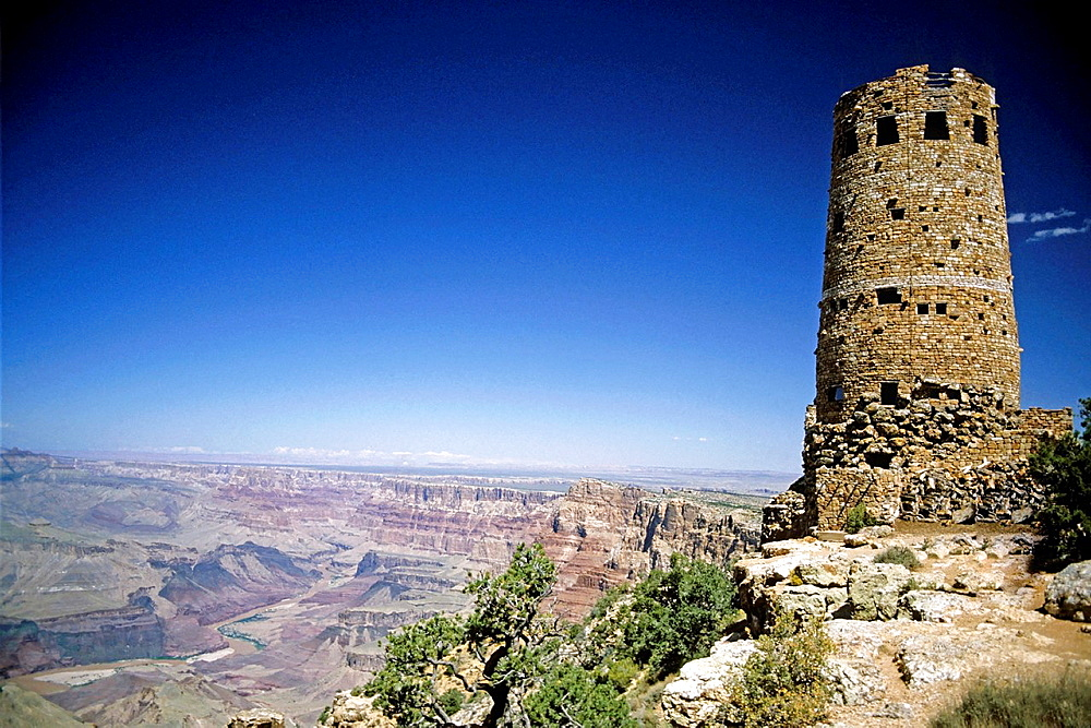 Historic stone structure of Colorado Tower and a wide view of Grand Canyon National Park, Arizona, USA