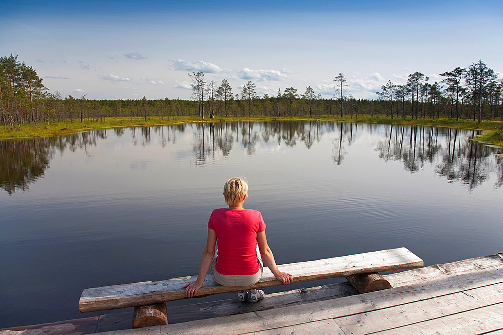 Young Woman Sitting by Bog Lake in Viru Bog, Lääne-Viru County, Estonia, Europe