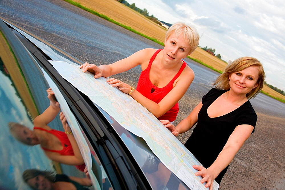 Young women on road trip and looking road map by car