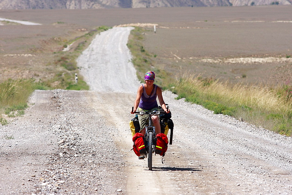 Female cyclist on a mountain road, leading from Kazarman to Naryn, Kyrgyzstan