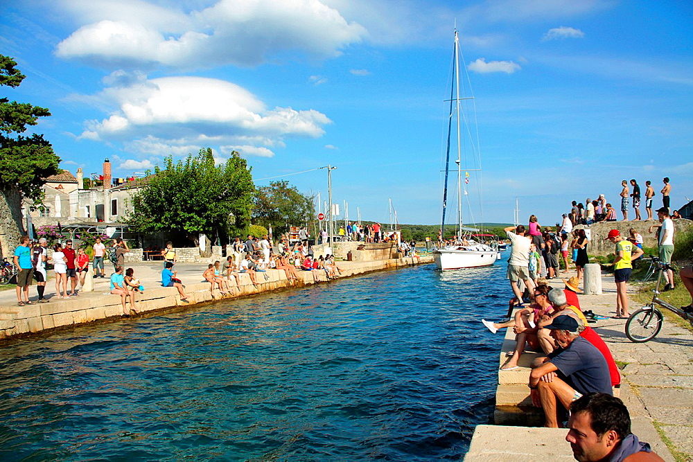 Tourists watching yachts sailing through canal between Cres Island and Losinij Island, Croatia