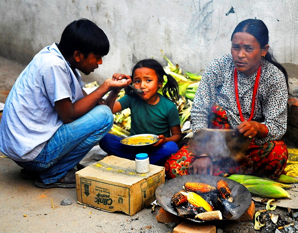 nepalese family selling corn on the cob to survive, the nepalis, life in kathmandu, kathmandu street life, nepal