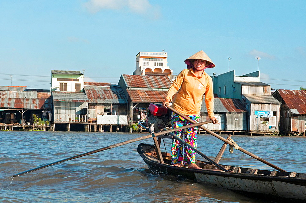 Vietnamese vendor rowing her boat at the Cai Rang Floating Market in the Mekong Delta in Vietnam