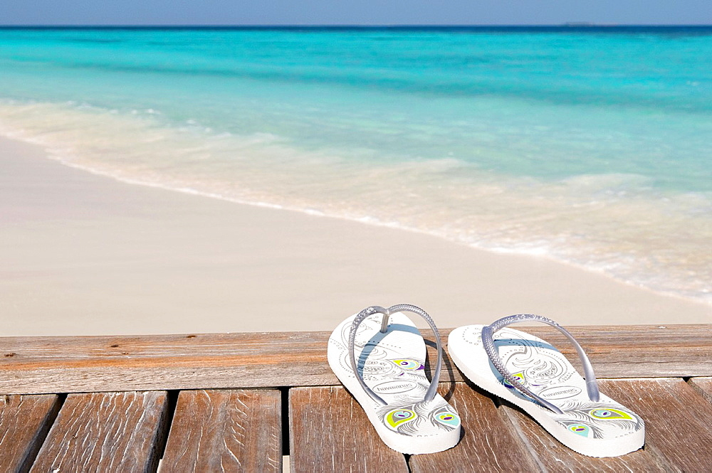 Flip flops on a jetty next to a white sand beach Maldives - 817-273400