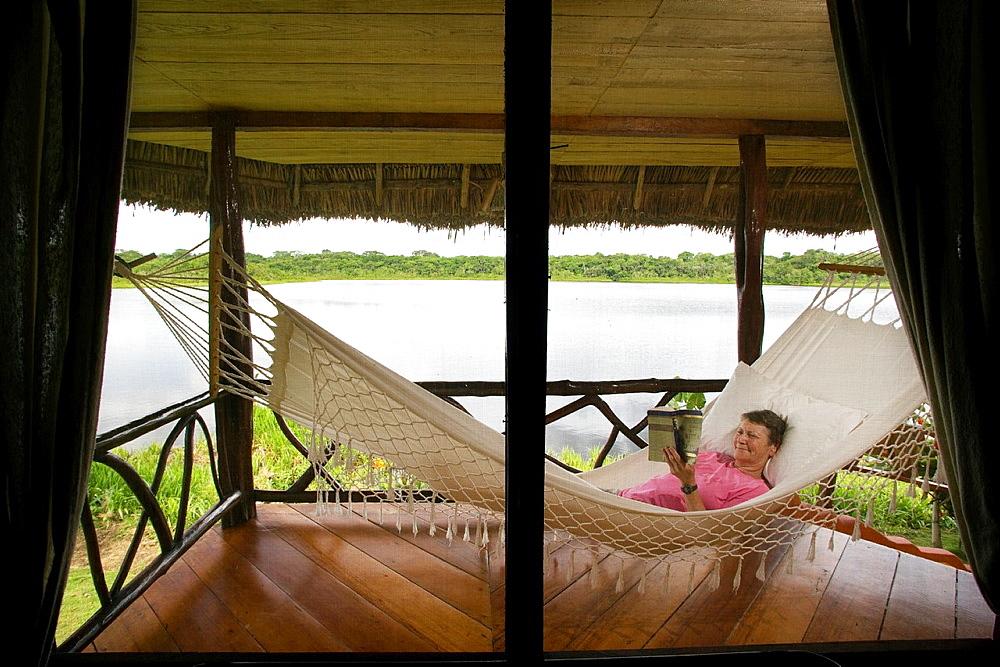 Woman reading in hammock, Napo Wildlife Center, Yasuni National Park, Napo Province, Ecuador
