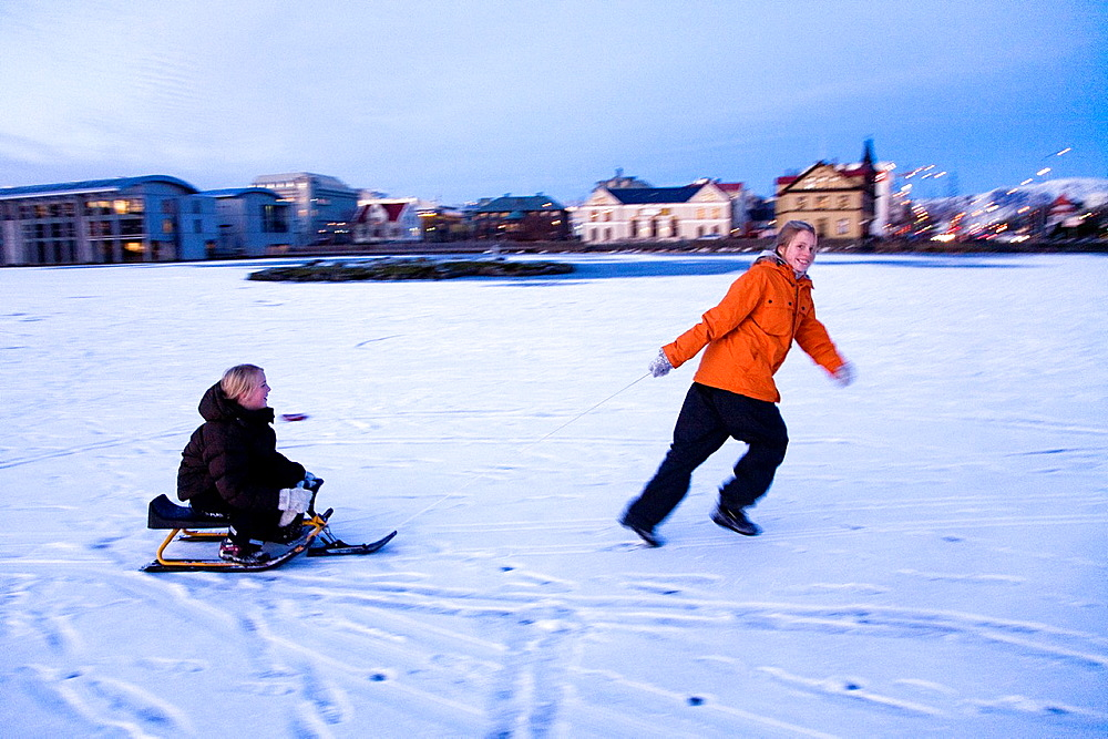 Two girls with a snow sled on a frozen lake Tjornin Downtown Reykjavik, Iceland