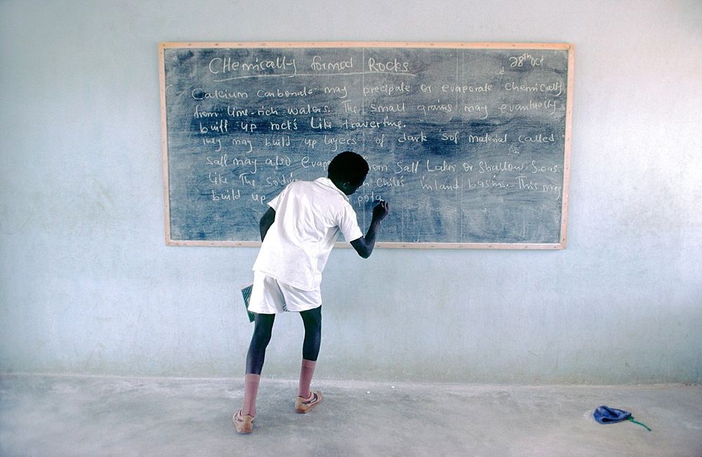 Nigerian schoolboy writing on chalk blackboard in classroom during geology lesson Nigeria