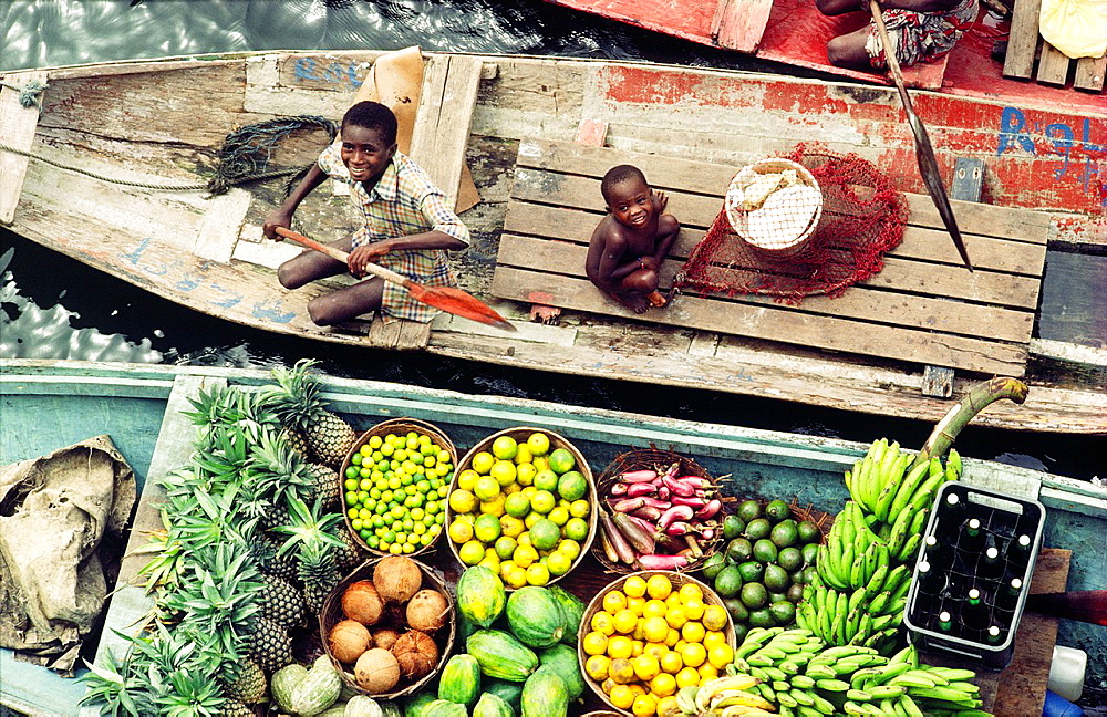 River Niger delta, Bendel State, Nigeria Boys sell fruit and beer from canoes at Bennett Island Anchorage on the Warri channel