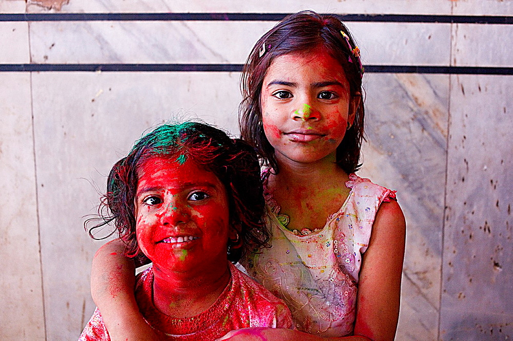 Friends celebrating the Holi spring festival to celebrate the love between Krishna and Radha, in Govind Devji temple, Jaipur, Rajasthan, India
