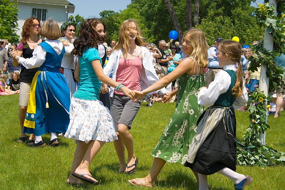 Teens dancing around the Maypole celebrating Midsommar at the Swedish Institute Midsommar Minneapolis Minnesota MN USA