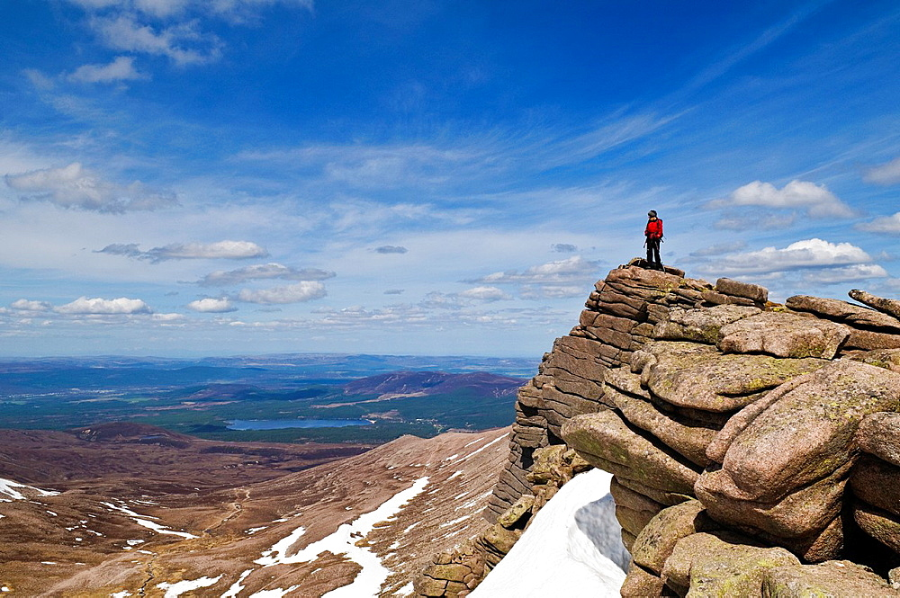 Female hiker stands on rocky outlook and enjoys view, Cairngorms national park, Scotland