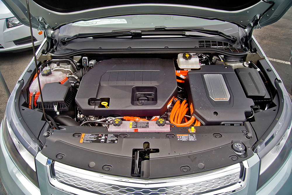 The engine compartment of a Chevrolet Volt hybrid gas/electric car Right side: the power inverter in top of the electric motor Left side: the 1 4-liter gasoline-powered engine used as generator to provide power to the electric motor or to engage mechani.