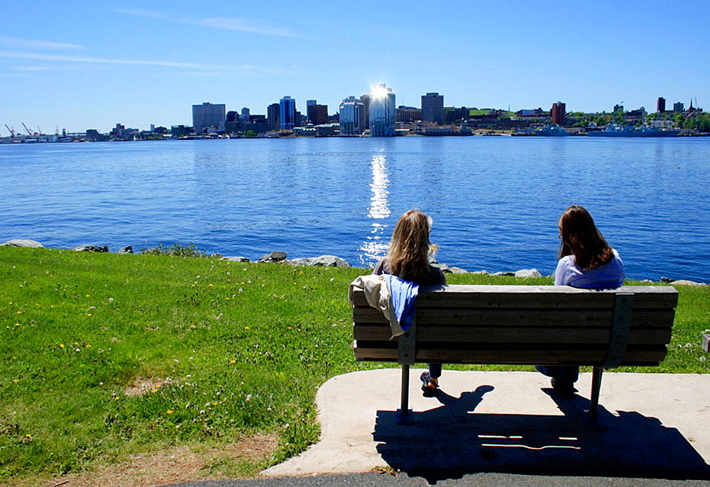2 girls sitting on bench, Dartmouth, Halifax, Nova Scotia, Canada.