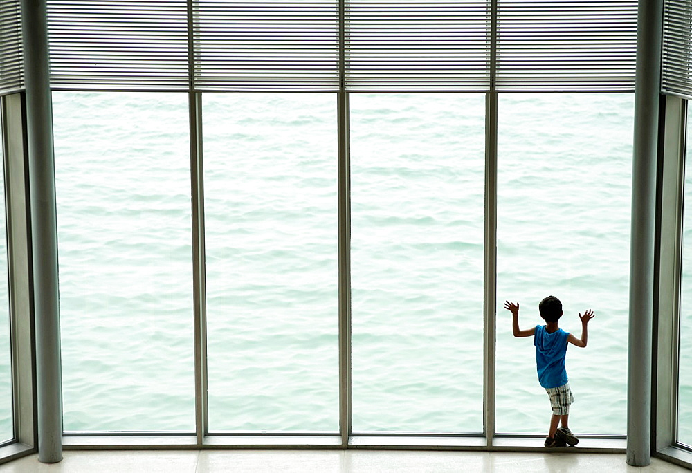 Boy looking out window at Museum of Islamic Art in Doha Qatar, architect IM Pei