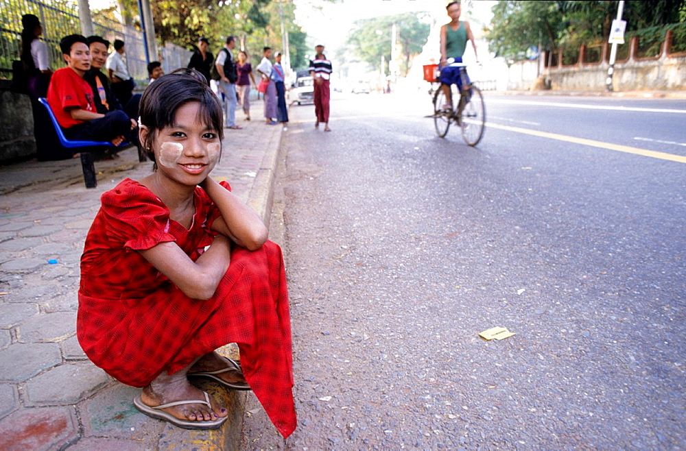Myanmar young woman sitting at a roadside in Rangon