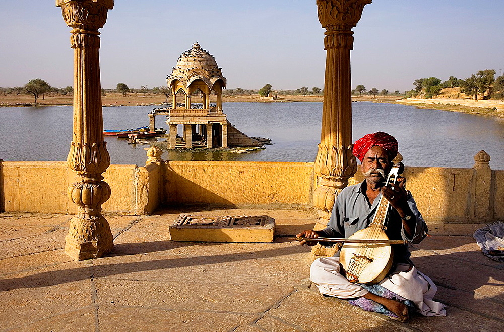 Musician in Gadi Sagar, the tank was once the water supply of the city and is surrounded by small temples and shrines, Jaisalmer,Rajasthan, India