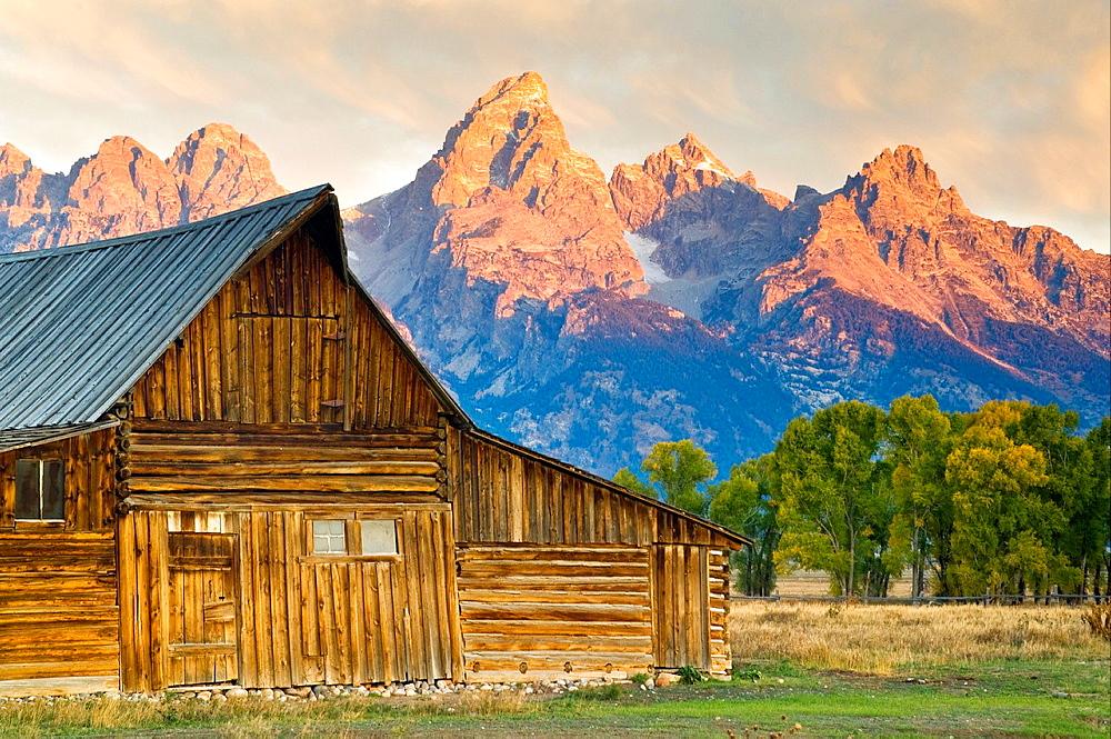 Sunrise light on the Grand teton mountain peak over old wooden barn, Mormon Row, Grand Teton National Park, Wyoming