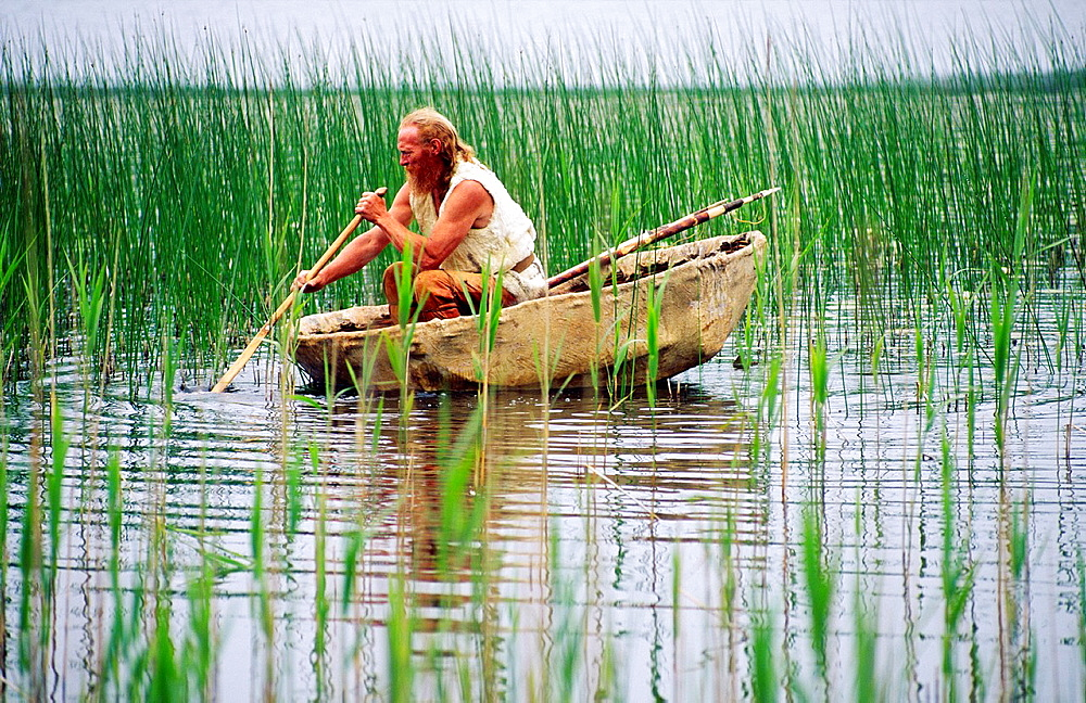 Neolithic re-enactment Stone Age man with fish spear paddling animal hide coracle boat on reed shore lake Kilmartin, Scotland